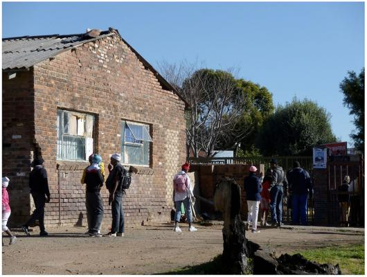 Figure 3a: Current after-school programs held in original eNtokozweni building. Despite minimal funding and management, after-school students gather outside the original structure. A drama team performs inside the existing building. An afte…