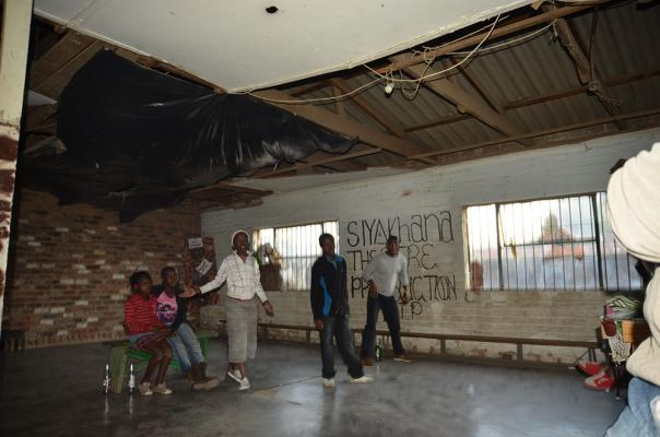 Figure 3b: Current after-school programs held in original eNtokozweni building. Despite minimal funding and management, after-school students gather outside the original structure. A drama team performs inside the existing building. An afte…